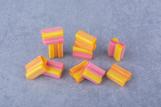 Poignée de morceaux de chewing-gum colorés sur une surface en marbre