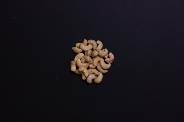 Une poignée de noix de cajou sur fond noir les noix sont pliées dans l'ordre