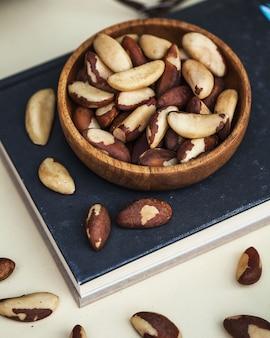Une poignée de noix du brésil dans une assiette en bois