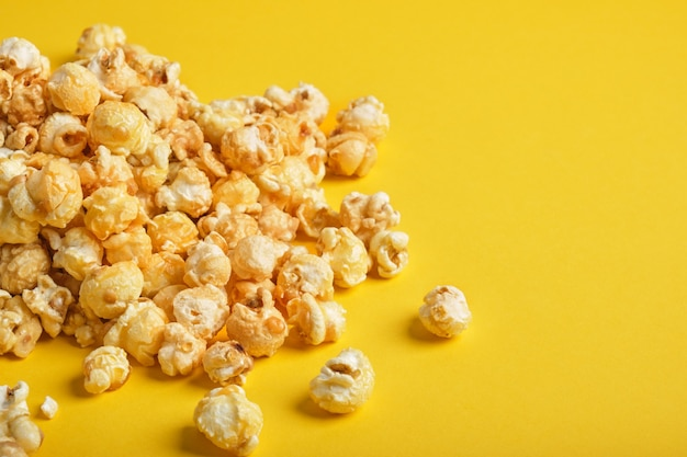 Une poignée de pop-corn sur fond jaune