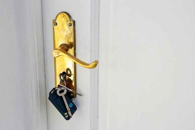 Poignée de porte dorée avec clés sur une porte blanche