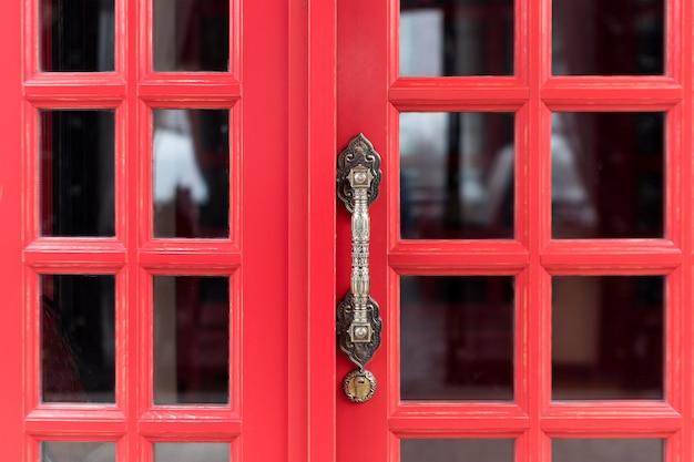 Poignée de porte en métal antique vintage sur porte en bois rouge.