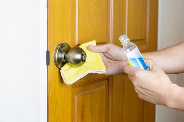 Poignée de porte de nettoyage à la main avec de l'alcool liquide