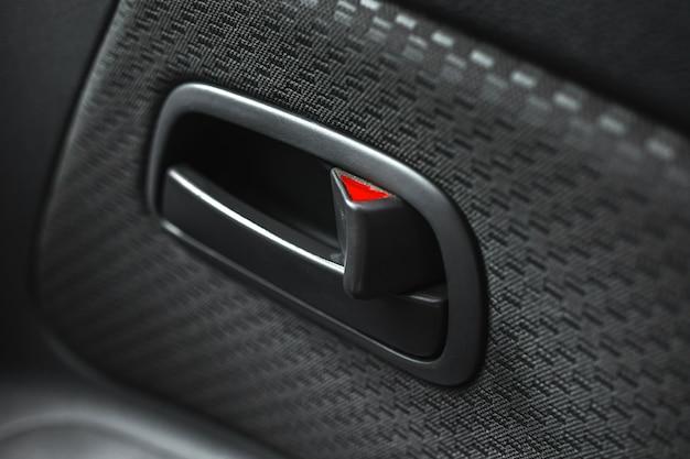 Poignée de porte de voiture à l'intérieur, photo en gros plan, intérieur de voiture moderne avec sellerie de luxe