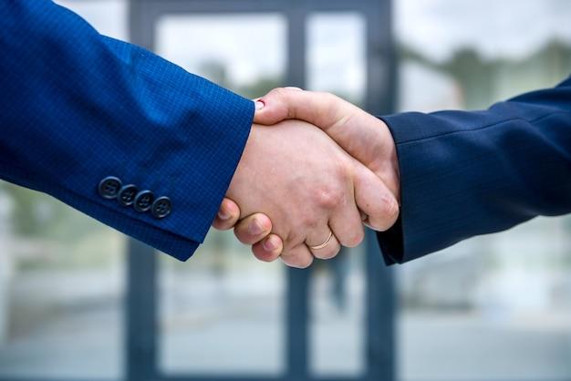 Poignées de main contre le nouveau centre d'affaires se bouchent