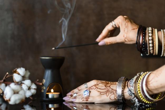 Poignets féminins peints avec des ornements de mehndi oriental indien traditionnel au henné. mains habillées de bracelets et bagues en métal tenant un bâton aromatique. lampe aromatique et fleurs de coton sur fond.