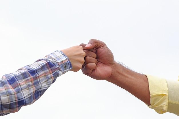 Poing bosse sur les vêtements de cérémonie, gesticulant un accord et coopération