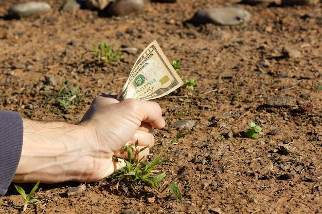 Poing de l'homme tenant un billet de dix dollars sur le sol sol sol investissement gros paris concepts de bonnes affaires