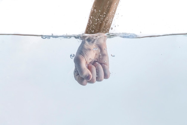 Le poing masculin attaque la main à travers la surface de l'eau, le mouvement de puissance de force