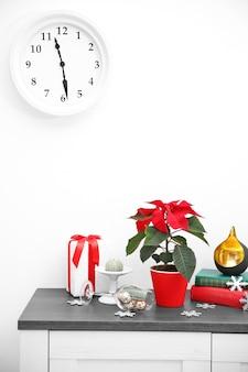 Poinsettia de fleurs de noël et décorations sur étagère avec décorations de noël, sur fond clair