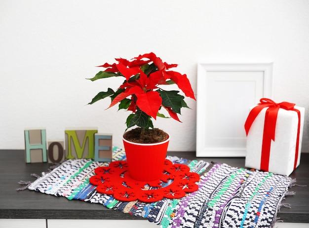Poinsettia de fleurs de noël et décorations sur étagère avec décorations de noël, sur mur clair