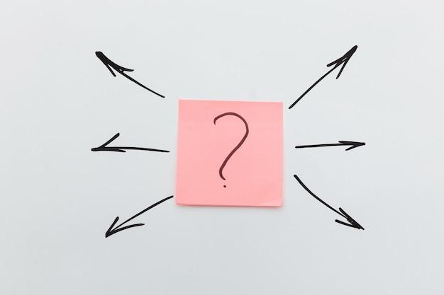 Point d'interrogation sur un autocollant et de nombreuses flèches. concept de choisir une direction