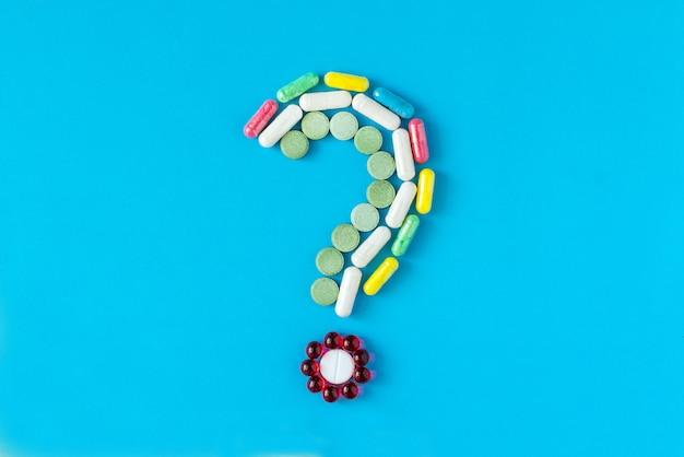 Point d'interrogation composé de différentes pilules de couleurs