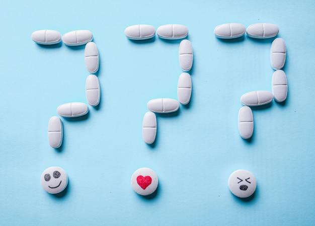 Point d'interrogation composé de pilules blanches sur une surface bleue. choix de traitement et concept de question.