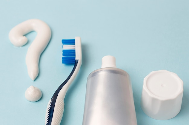 Point d'interrogation de dentifrice et brosse à dents sur bleu