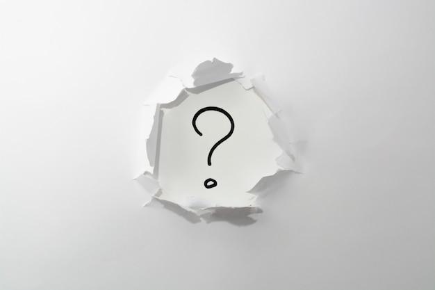 Point d'interrogation sur un fond blanc dans un trou de papier.