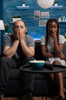 Point de vue d'un couple interracial choqué en regardant un film dramatique à la télévision dans le salon. partenaires de race mixte avec les mains sur la bouche en regardant la caméra et la télévision. amoureux multiethniques