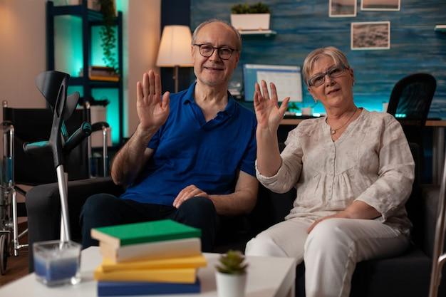 Point de vue d'un couple de personnes âgées agitant les mains lors d'une conférence téléphonique vidéo
