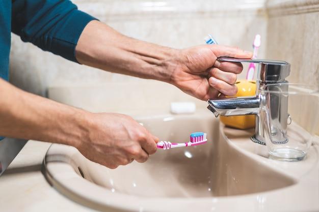 Point de vue de l'homme se brossant les dents dans la salle de bain.