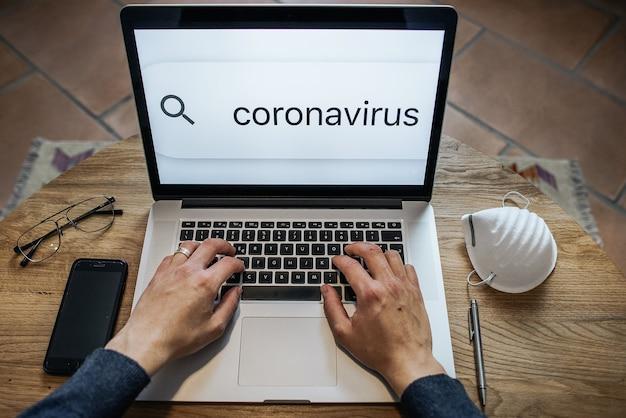 Point de vue mains d'homme coupées tapant sur un clavier d'ordinateur portable surfant sur internet à la recherche d'informations sur le coronavirus