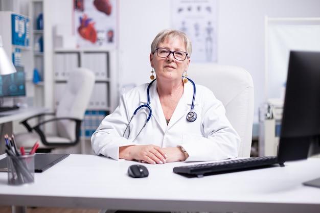 Point de vue d'un médecin parlant en ligne avec des patients assis dans une chambre d'hôpital regardant la caméra portant une blouse de laboratoire et un stéthoscope. consultation d'un médecin par appel vidéo parlant à distance par webcam télémédecine