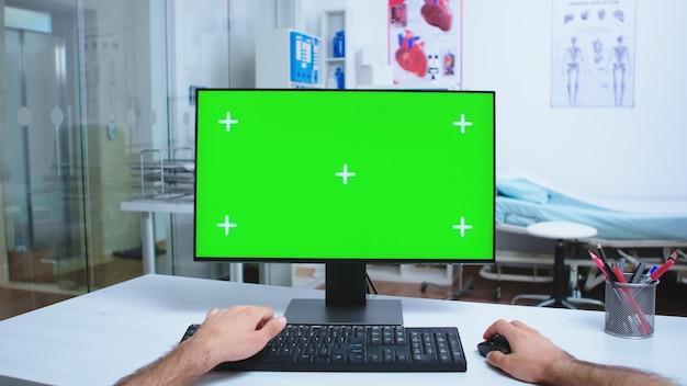 Point de vue d'un médecin travaillant sur un ordinateur avec une clé chroma dans le cabinet de l'hôpital et un médecin quittant le bureau de la clinique. médecin dans le bureau de travail du cabinet de la clinique avec espace de copie disponible.