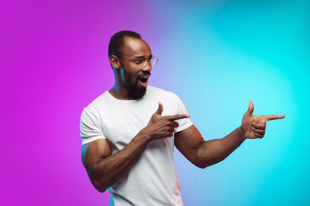 Pointage montrant le portrait d'un jeune homme afro-américain sur fond de studio dégradé en néon