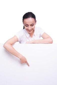 Pointage de votre produit. belle jeune femme se penchant sur l'espace de copie et le pointant tout en isolé sur blanc
