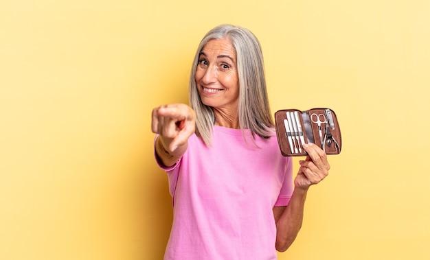 Pointant la caméra avec un sourire satisfait, confiant et amical, vous choisissant tenant un étui à outils pour les ongles