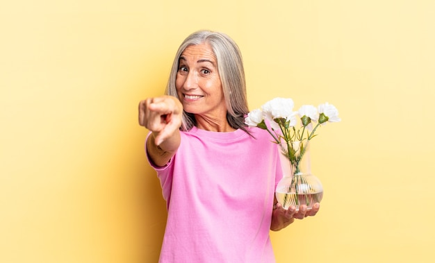 Pointant la caméra avec un sourire satisfait, confiant et amical, vous choisissant tenant des fleurs décoratives