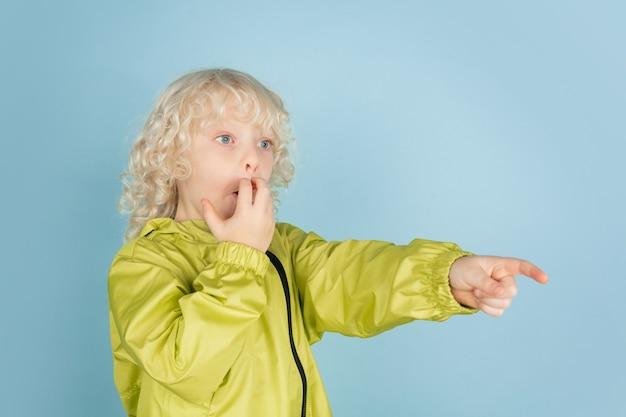 Pointant sur le côté. portrait de beau petit garçon caucasien isolé sur mur bleu. modèle masculin blond bouclé. concept d'expression faciale, émotions humaines, enfance, copyspace.