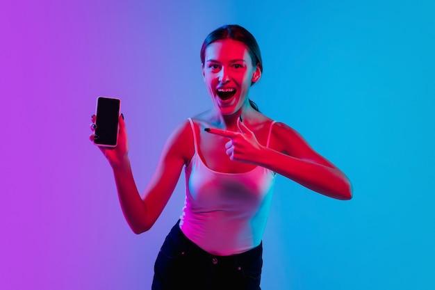Pointant sur le téléphone. portrait de jeune femme caucasienne sur fond de studio dégradé bleu-violet à la lumière du néon. concept de jeunesse, émotions humaines, expression faciale, ventes, publicité. beau modèle brune.