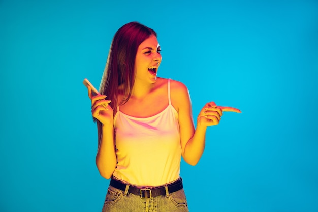 Pointant avec le téléphone, souriant. portrait de jeune femme caucasienne sur fond bleu à la lumière du néon. beau modèle féminin en casual. concept d'émotions humaines, d'expression faciale, de ventes, d'annonces. espace de copie.