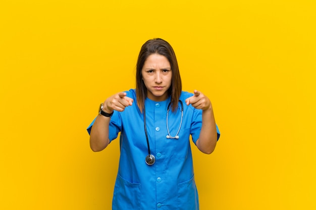 Pointant vers l'avant avec les deux doigts et une expression de colère, vous demandant de faire votre devoir isolé contre le mur jaune