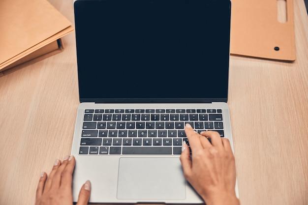 Pointe de vue d'une femme utilisant un ordinateur dans le bureau tout en se connectant à internet wifi