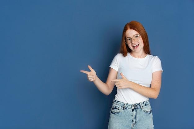 Pointer, choisir. portrait de jeune fille caucasienne sur mur bleu.