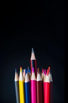Les pointes de crayons de couleur et au centre d'un simple crayon sur fond noir