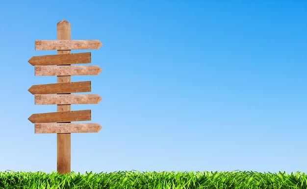 Pointeur en bois sur l'arrière-plan pelouse dans un ciel clair