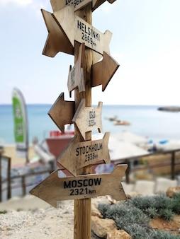 Pointeur de route en bois montrant le chemin vers les différentes villes du monde. panneau en bois vers moscou, stockholm, oslo, helsinki donné en kilomètres.