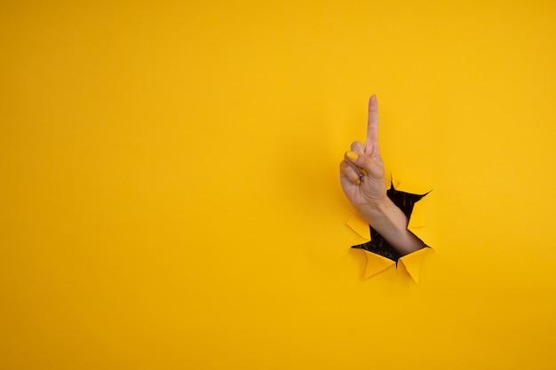 Pointez la main sur quelque chose qui sort d'un trou dans du papier jaune déchiré.