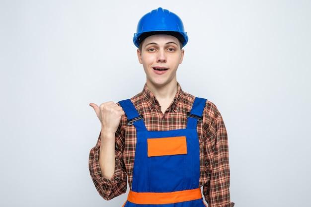 Points heureux à côté du jeune constructeur masculin en uniforme