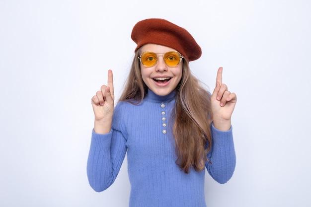 Points impressionnés par la belle petite fille portant des lunettes avec un chapeau isolé sur un mur blanc
