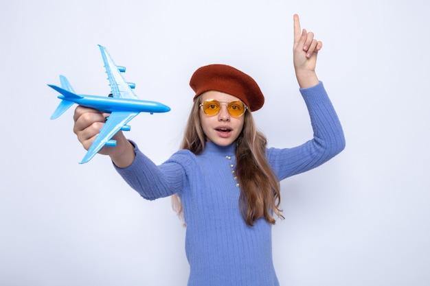 Points impressionnés par la belle petite fille portant des lunettes avec un chapeau tenant un avion jouet isolé sur un mur blanc
