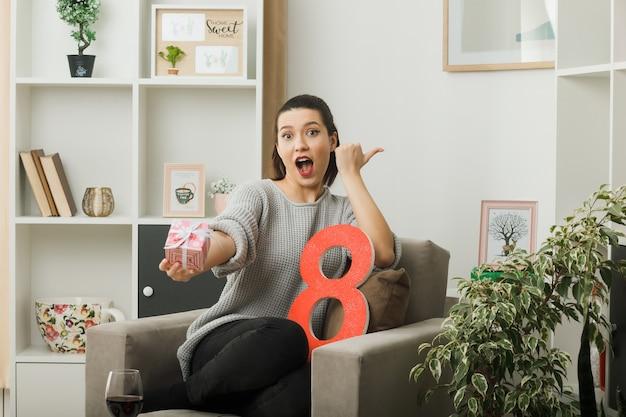 Points surpris à côté de la belle fille le jour de la femme heureuse tenant un présent à la caméra assis sur un fauteuil dans le salon