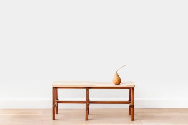 Poire brune sur un banc en bois dans une salle blanche