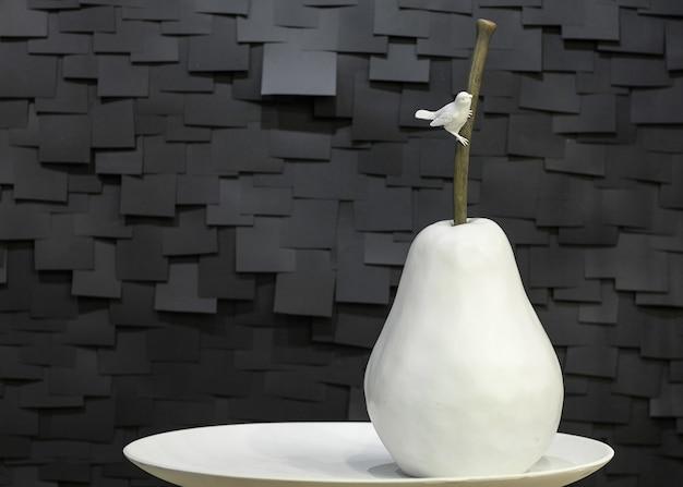 Poire en céramique artificielle d'un plat avec un oiseau sur un fond noir sous forme de tuiles