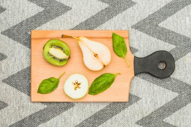 Poire coupée en deux; tranche de pomme et feuilles de basilic sur une planche à découper en bois