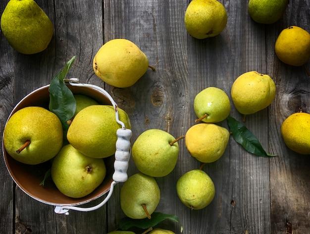 Poire jaune mûre sur une surface en bois grise et seau en fer