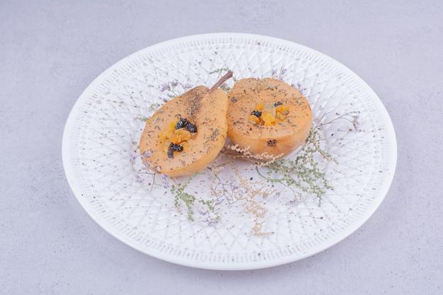 Poire pelée et tranchée aux herbes et épices dans une assiette blanche