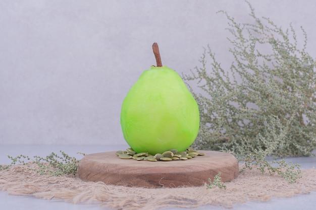 Une poire verte avec des graines de citrouille autour.